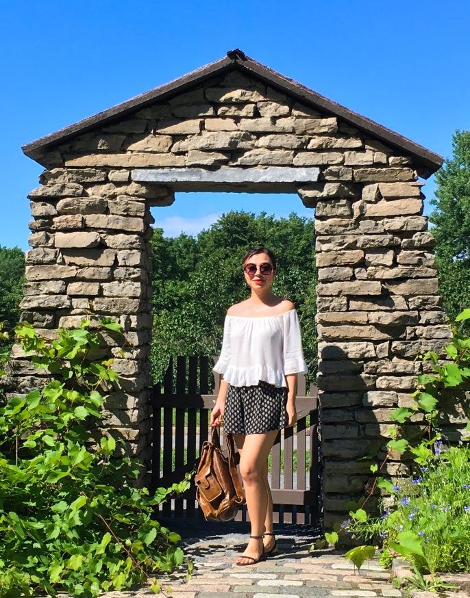 Montreal Botanical Garden stone arbor gate Urban Planet off-the-shoulder top Forever 21 shorts sunglasses Asos sandals leather backpack