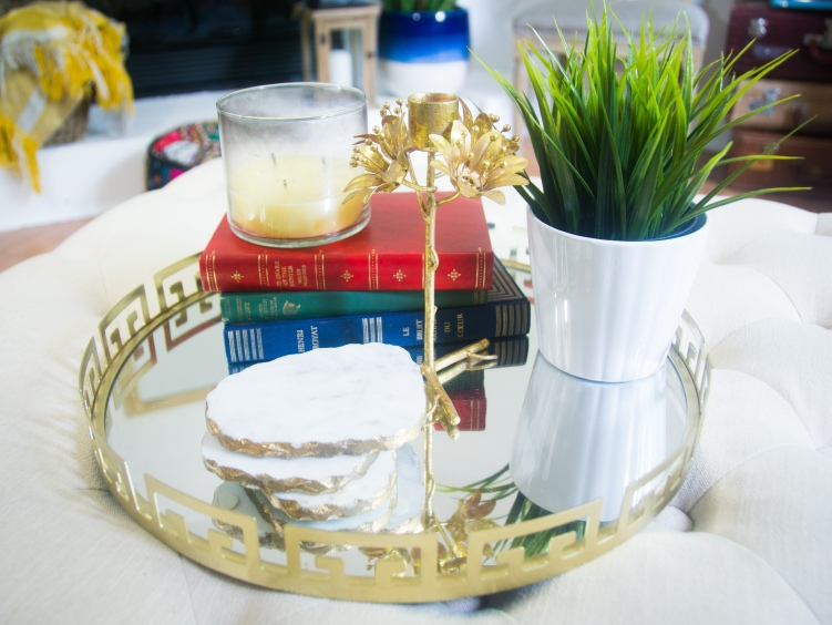 gold mirrored tray tufted ottoman coffee table faux plant vintage books gold candle holder marble coasters eclectic antique bohemian home living room decor